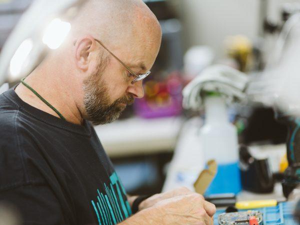 Service Programs. Man repairing equipment.